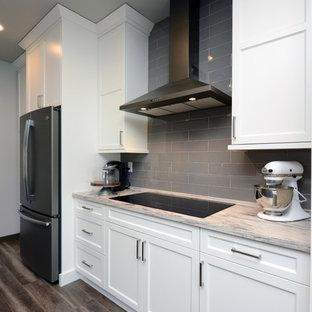 他の地域の小さいカントリー風おしゃれなキッチン (アンダーカウンターシンク、シェーカースタイル扉のキャビネット、白いキャビネット、人工大理石カウンター、グレーのキッチンパネル、セラミックタイルのキッチンパネル、シルバーの調理設備の、ラミネートの床、茶色い床、ベージュのキッチンカウンター) の写真