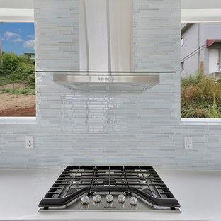 Inredning av ett modernt mellanstort kök, med en dubbel diskho, släta luckor, vita skåp, bänkskiva i kvarts, grått stänkskydd, stänkskydd i glaskakel, rostfria vitvaror, ljust trägolv och en köksö