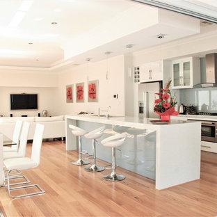 Idéer för ett mellanstort modernt kök, med en undermonterad diskho, släta luckor, vita skåp, bänkskiva i kvarts, grönt stänkskydd, glaspanel som stänkskydd, rostfria vitvaror, mellanmörkt trägolv, en köksö och gult golv