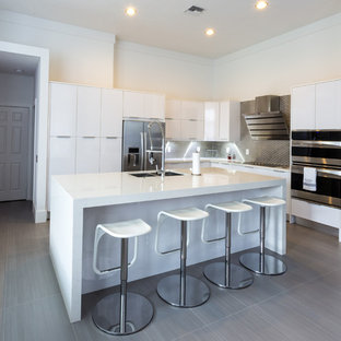 Eat-in kitchen - large modern l-shaped porcelain floor eat-in kitchen idea in Miami with a double-bowl sink, flat-panel cabinets, white cabinets, quartz countertops, metallic backsplash, metal backsplash, stainless steel appliances and an island
