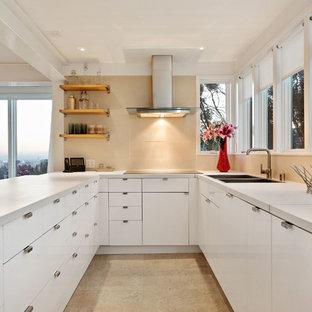 ロサンゼルスの大きいコンテンポラリースタイルのおしゃれなキッチン (ダブルシンク、フラットパネル扉のキャビネット、白いキャビネット、ベージュキッチンパネル、人工大理石カウンター、磁器タイルのキッチンパネル、シルバーの調理設備の、ベージュの床) の写真