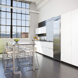 Minimalist single-wall kitchen photo in San Francisco with stainless steel appliances, flat-panel cabinets and white cabinets