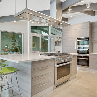 Modern eat-in kitchen designs - Inspiration for a modern l-shaped eat-in kitchen remodel in Orange County with an undermount sink, flat-panel cabinets, light wood cabinets, paneled appliances, an island and white countertops