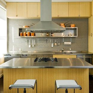 他の地域の小さいコンテンポラリースタイルのおしゃれなキッチン (一体型シンク、フラットパネル扉のキャビネット、淡色木目調キャビネット、ステンレスカウンター、グレーのキッチンパネル、シルバーの調理設備の、濃色無垢フローリング、茶色い床) の写真