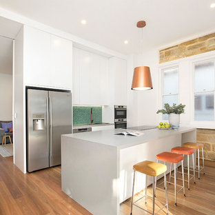 Contemporary single-wall kitchen in Sydney with white cabinets, green splashback, stainless steel appliances, medium hardwood floors, with island, brown floor, grey benchtop, an undermount sink, flat-panel cabinets, solid surface benchtops and mosaic tile splashback.