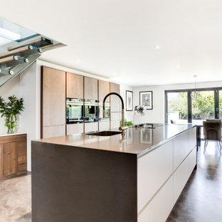 サセックスの大きいコンテンポラリースタイルのおしゃれなキッチン (シングルシンク、フラットパネル扉のキャビネット、中間色木目調キャビネット、黒い調理設備、ベージュの床、青いキッチンカウンター) の写真