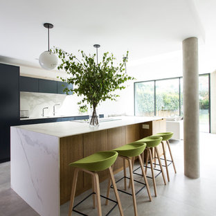 This is an example of an expansive modern galley open plan kitchen in London with flat-panel cabinets, black cabinets, marble worktops, white splashback, marble splashback, concrete flooring, an island, grey floors, a submerged sink and white worktops.