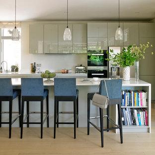Cette image montre une cuisine design avec un placard à porte plane, des portes de placard grises, un électroménager en acier inoxydable, un sol en bois clair et un îlot central.