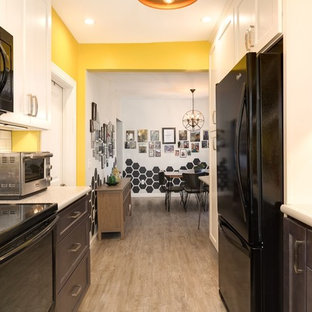 This is an example of a small midcentury galley eat-in kitchen in Providence with a drop-in sink, flat-panel cabinets, white cabinets, laminate benchtops, white splashback, subway tile splashback, black appliances, vinyl floors, no island and grey floor.