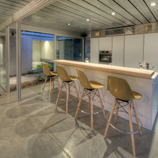 Urban galley kitchen photo in San Francisco with wood countertops, flat-panel cabinets and white cabinets