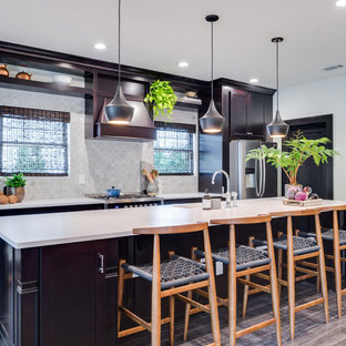 This is an example of a mid-sized tropical single-wall eat-in kitchen in Orange County with an undermount sink, shaker cabinets, dark wood cabinets, laminate benchtops, grey splashback, ceramic splashback, stainless steel appliances, medium hardwood floors and with island.