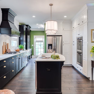 Transitional kitchen remodeling - Transitional u-shaped dark wood floor and brown floor kitchen photo in Austin with an undermount sink, flat-panel cabinets, black cabinets, white backsplash, stainless steel appliances, an island and white countertops
