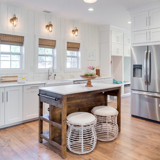 Mid-sized farmhouse eat-in kitchen inspiration - Mid-sized cottage u-shaped medium tone wood floor and brown floor eat-in kitchen photo in Orange County with a farmhouse sink, shaker cabinets, white cabinets, quartz countertops, white backsplash, marble backsplash, stainless steel appliances, an island and white countertops