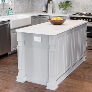 Mid-sized transitional kitchen designs - Example of a mid-sized transitional u-shaped medium tone wood floor and brown floor kitchen design in Orange County with a farmhouse sink, raised-panel cabinets, white cabinets, stainless steel appliances, an island, quartz countertops, gray backsplash and white countertops