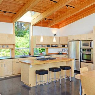 Diseño de cocina en L, actual, abierta, con electrodomésticos de acero inoxidable, encimera de madera, armarios con paneles lisos y puertas de armario de madera clara