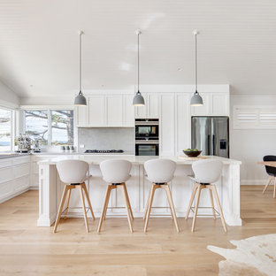 Large transitional l-shaped kitchen in Sydney with a drop-in sink, shaker cabinets, white cabinets, stainless steel appliances, light hardwood floors, with island, beige floor and white benchtop.