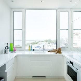 Свежая идея для дизайна: п-образная кухня в современном стиле с врезной раковиной, плоскими фасадами, белыми фасадами, бежевым полом и белой столешницей - отличное фото интерьера