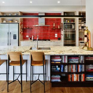 クライストチャーチの中サイズのエクレクティックスタイルのおしゃれなキッチン (ダブルシンク、フラットパネル扉のキャビネット、淡色木目調キャビネット、御影石カウンター、赤いキッチンパネル、セラミックタイルのキッチンパネル、シルバーの調理設備の、無垢フローリング、マルチカラーのキッチンカウンター) の写真