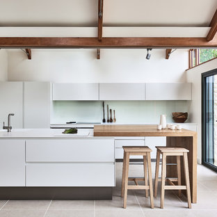 Photo of a large country galley kitchen in Other with an integrated sink, porcelain flooring, beige floors, flat-panel cabinets, white cabinets, green splashback, glass sheet splashback, a breakfast bar and white worktops.