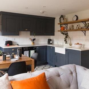 サセックスの中サイズのエクレクティックスタイルのおしゃれなキッチン (エプロンフロントシンク、シェーカースタイル扉のキャビネット、黒いキャビネット、人工大理石カウンター、白いキッチンパネル、セラミックタイルのキッチンパネル、黒い調理設備、クッションフロア、アイランドなし) の写真