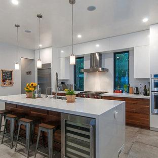 Diseño de cocina de galera, moderna, de tamaño medio, cerrada, con armarios con paneles lisos, puertas de armario blancas, encimera de cuarzo compacto, electrodomésticos de acero inoxidable, suelo de azulejos de cemento, una isla y suelo gris