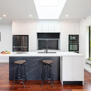 This is an example of a mid-sized transitional galley open plan kitchen in Perth with an undermount sink, shaker cabinets, white cabinets, quartz benchtops, grey splashback, stone slab splashback, black appliances, medium hardwood floors, with island, white benchtop and brown floor.