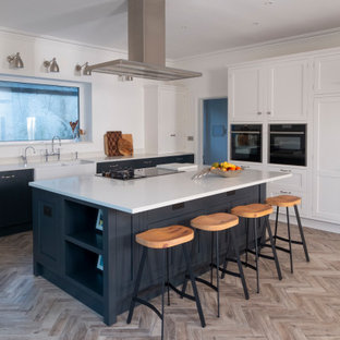 This is an example of a large classic l-shaped kitchen in Cardiff with a belfast sink, shaker cabinets, white cabinets, integrated appliances, an island, beige floors and white worktops.