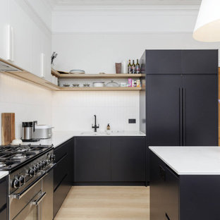 Inspiration for a mid-sized contemporary l-shaped eat-in kitchen in Edinburgh with quartz benchtops, white splashback, ceramic splashback, laminate floors, with island, white benchtop, black cabinets, panelled appliances, beige floor and coffered.
