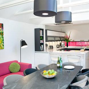 Imagen de cocina comedor en U, contemporánea, grande, con salpicadero rosa, salpicadero de vidrio templado, península, armarios con paneles lisos, puertas de armario negras, encimera de acrílico, suelo de baldosas de porcelana y suelo gris