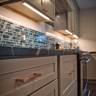 This is an example of a mid-sized country l-shaped eat-in kitchen in Other with a single-bowl sink, shaker cabinets, grey cabinets, soapstone benchtops, blue splashback, glass tile splashback, stainless steel appliances, vinyl floors, with island, brown floor and multi-coloured benchtop.