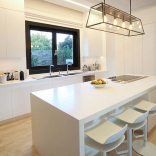 Medium sized contemporary single-wall kitchen in Surrey with a double-bowl sink, flat-panel cabinets, white cabinets, light hardwood flooring, an island, beige floors and white worktops.
