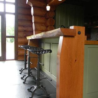 モントリオールの中サイズのラスティックスタイルのおしゃれなキッチン (シングルシンク、シェーカースタイル扉のキャビネット、緑のキャビネット、グレーのキッチンパネル、石タイルのキッチンパネル、シルバーの調理設備の、スレートの床、木材カウンター) の写真