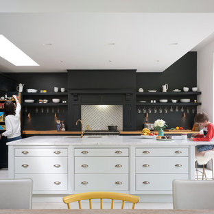 Traditional l-shaped open plan kitchen in Kent with a built-in sink, flat-panel cabinets, black cabinets, marble worktops, white splashback, cement tile splashback, integrated appliances, ceramic flooring and a breakfast bar.