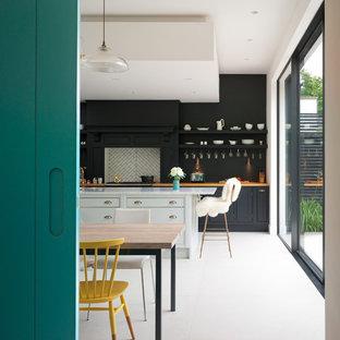 ケントのエクレクティックスタイルのおしゃれなキッチン (ドロップインシンク、大理石カウンター、フラットパネル扉のキャビネット、白いキッチンパネル、セメントタイルのキッチンパネル、パネルと同色の調理設備、セラミックタイルの床、黒いキャビネット) の写真