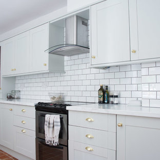 Design ideas for a mid-sized traditional galley eat-in kitchen in Cambridgeshire with a double-bowl sink, shaker cabinets, grey cabinets, laminate benchtops, white splashback, ceramic splashback, black appliances, terra-cotta floors, no island, orange floor and white benchtop.
