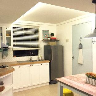 他の地域の小さいビーチスタイルのおしゃれなキッチン (一体型シンク、ガラス扉のキャビネット、白いキャビネット、タイルカウンター、白いキッチンパネル、セラミックタイルのキッチンパネル、シルバーの調理設備の、磁器タイルの床、アイランドなし、ベージュの床、茶色いキッチンカウンター) の写真
