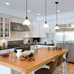 Cette image montre une cuisine marine en L avec un évier de ferme, un placard à porte vitrée, des portes de placard blanches, un plan de travail en granite, une crédence blanche, une crédence en carreau de porcelaine et un électroménager en acier inoxydable.