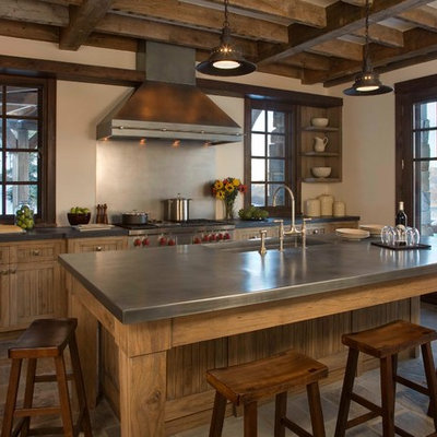 Example of a mid-sized mountain style galley slate floor and brown floor enclosed kitchen design in New York with an undermount sink, medium tone wood cabinets, stainless steel countertops, metallic backsplash, shaker cabinets, stainless steel appliances and an island