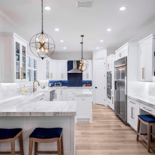 Transitional u-shaped medium tone wood floor and brown floor eat-in kitchen photo in Tampa with marble countertops, an island, white countertops, a farmhouse sink, shaker cabinets, white cabinets, blue backsplash and stainless steel appliances