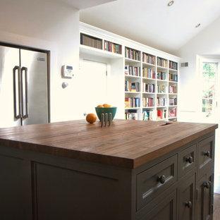 ニューヨークのエクレクティックスタイルのおしゃれなキッチン (アンダーカウンターシンク、シェーカースタイル扉のキャビネット、グレーのキャビネット、木材カウンター、白いキッチンパネル、セラミックタイルのキッチンパネル、シルバーの調理設備、濃色無垢フローリング) の写真