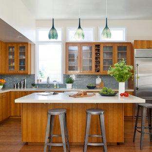 Inspiration för ett stort funkis kök, med en undermonterad diskho, luckor med glaspanel, skåp i mellenmörkt trä, bänkskiva i kvarts, blått stänkskydd, stänkskydd i keramik, rostfria vitvaror, en köksö, bambugolv och brunt golv