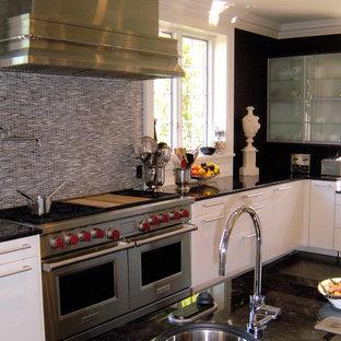 ニューヨークの巨大なエクレクティックスタイルのおしゃれなキッチン (アンダーカウンターシンク、フラットパネル扉のキャビネット、白いキャビネット、マルチカラーのキッチンパネル、ボーダータイルのキッチンパネル、シルバーの調理設備の、濃色無垢フローリング) の写真