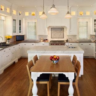 デンバーの大きいヴィクトリアン調のおしゃれなキッチン (シルバーの調理設備の、落し込みパネル扉のキャビネット、白いキャビネット、アンダーカウンターシンク、大理石カウンター、白いキッチンパネル、石スラブのキッチンパネル、無垢フローリング) の写真