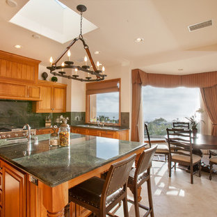 This is an example of a traditional eat-in kitchen in San Diego with raised-panel cabinets, medium wood cabinets, green splashback, stone slab splashback, stainless steel appliances and green benchtop.