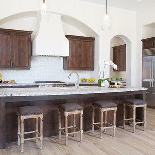 Offene, Einzeilige, Große Moderne Küche mit Einbauwaschbecken, Schrankfronten mit vertiefter Füllung, braunen Schränken, Granit-Arbeitsplatte, Küchenrückwand in Weiß, Küchengeräten aus Edelstahl, Porzellan-Bodenfliesen und Kücheninsel in Phoenix