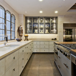 Inspiration pour une cuisine méditerranéenne avec un placard à porte vitrée, un électroménager en acier inoxydable et un évier 2 bacs.