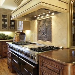 Diseño de cocina mediterránea con encimera de cobre, puertas de armario de madera en tonos medios, salpicadero beige, electrodomésticos negros y salpicadero de piedra caliza