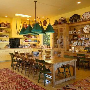 Eclectic eat-in kitchen photos - Inspiration for an eclectic l-shaped eat-in kitchen remodel in Santa Barbara with flat-panel cabinets, yellow cabinets, black backsplash and black appliances
