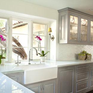 Inspiration för stora klassiska kök, med en rustik diskho, luckor med upphöjd panel, grå skåp, bänkskiva i glas, vitt stänkskydd, stänkskydd i keramik, rostfria vitvaror, mörkt trägolv och en köksö