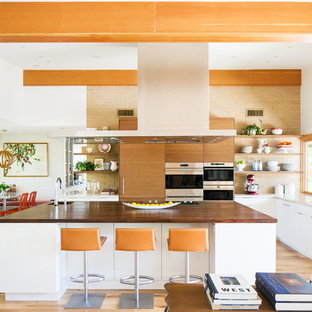 Design ideas for a midcentury l-shaped open plan kitchen in Phoenix with light hardwood floors, with island, a double-bowl sink, flat-panel cabinets, medium wood cabinets, wood benchtops, orange splashback, brick splashback, stainless steel appliances, beige floor and brown benchtop.